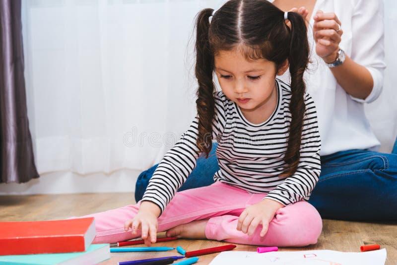 Gl?ckliche Kinderkinderm?dchensohn-Kindergartenzeichnung auf peper Lehrerausbildung mit sch?ner Mutter lizenzfreie stockfotos