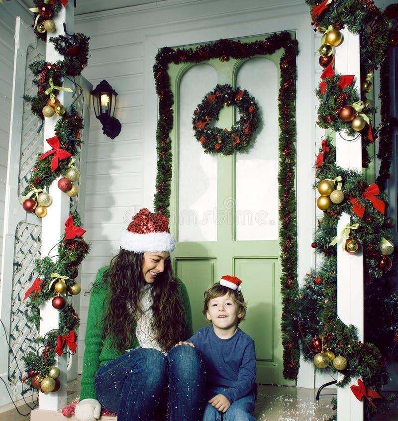 Gl?ckliche l?chelnde Familie auf Weihnachten am Haus mit Geschenken, junger Mutter und kleinem Sohn in rotem Hut Sankt, Lebenssti lizenzfreies stockbild