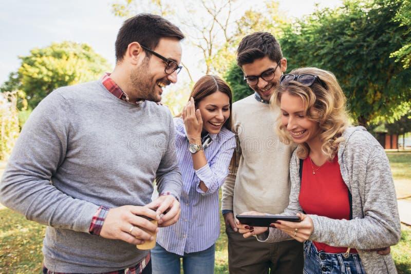 Gl?ckliche l?chelnde junge Freunde, die drau?en in den Park h?lt digitale Tablette gehen stockfotos