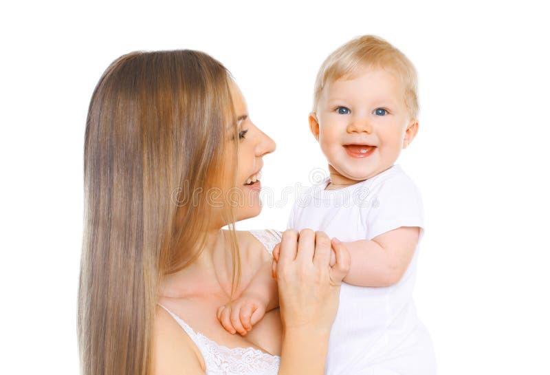 Gl?ckliche l?chelnde Mutter und Baby der Portr?tnahaufnahme, die den Spa? zusammen lokalisiert auf Wei? hat stockbilder