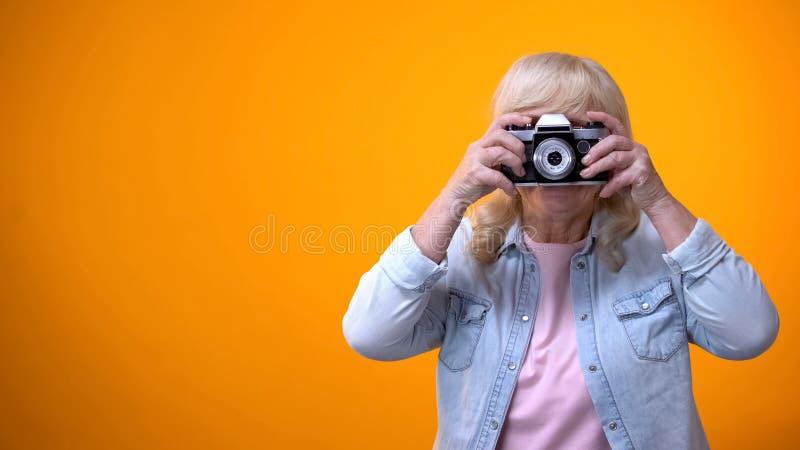 Gl?ckliche l?chelnde Rentnerfrau, die Foto, Hobby und Entspannung, Freizeit nimmt stockfotos