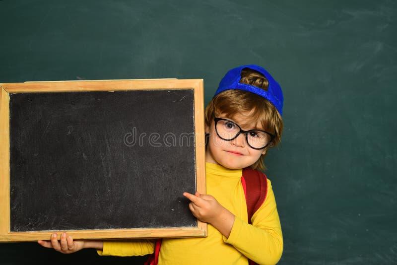 Gl?ckliche l?chelnde Sch?ler, die am Schreibtisch zeichnen Freundliches l?chelndes Kind an der Tafel Klassenzimmer Pupillen an ei lizenzfreie stockfotografie