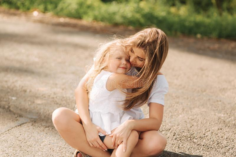 Gl?ckliche liebevolle Familie Bemuttern Sie und ihr spielendes und umarmendes Tochterkinderm?dchen Gasse von gro?en B?umen Weiche stockfotos