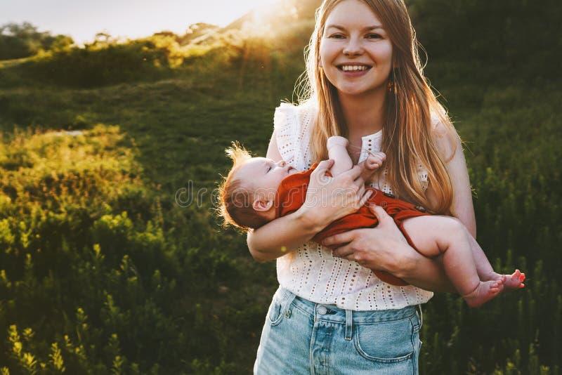 Gl?ckliche Mutter, die mit Familienlebensstil des S?uglingsbabys im Freien geht stockfotos