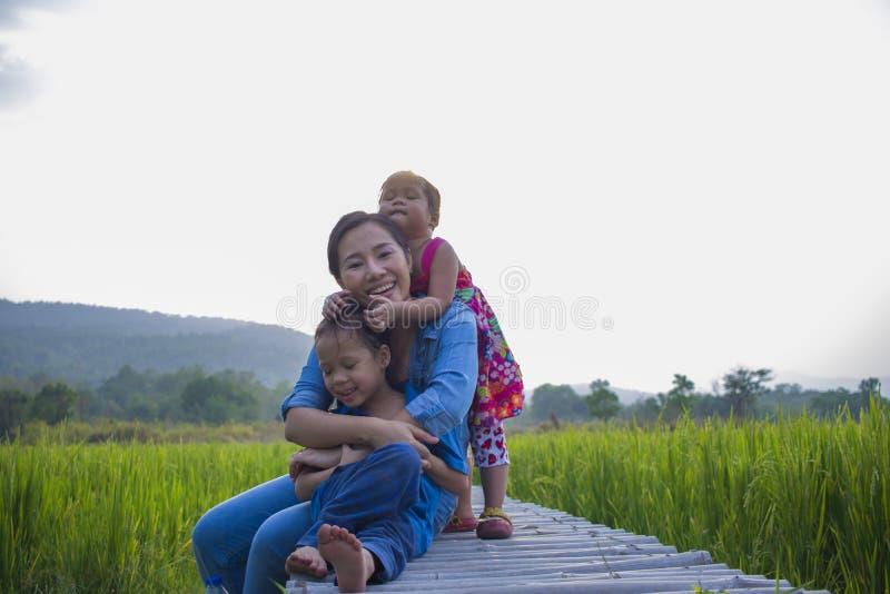 Gl?ckliche Mutter und ihr Kinderspiel, die drau?en Spa?, hinteren Boden des gr?nen Reisfeldes hat stockfoto