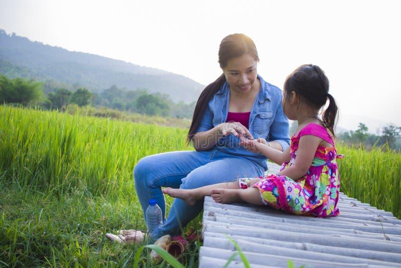 Gl?ckliche Mutter und ihr Kinderspiel, die drau?en Spa?, hinteren Boden des gr?nen Reisfeldes hat stockfotografie