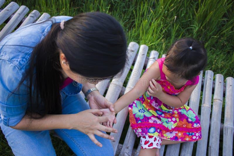 Gl?ckliche Mutter und ihr Kinderspiel, die drau?en Spa?, hinteren Boden des gr?nen Reisfeldes hat lizenzfreie stockfotografie