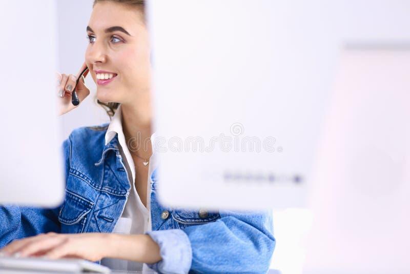 Gl?ckliche reizend junge Frau, die mit Laptop unter Verwendung des Kopfh?rers im B?ro sitzt und arbeitet stockfotos