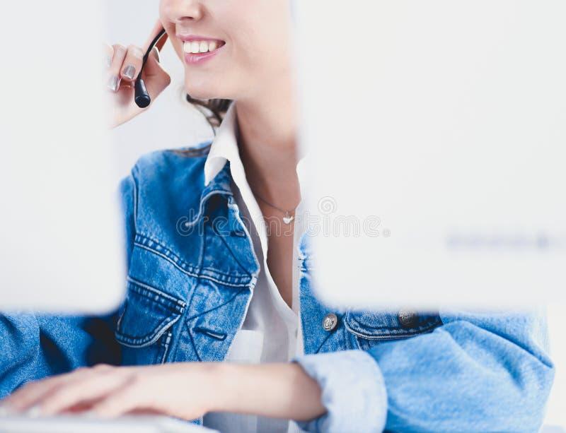 Gl?ckliche reizend junge Frau, die mit Laptop unter Verwendung des Kopfh?rers im B?ro sitzt und arbeitet lizenzfreie stockbilder