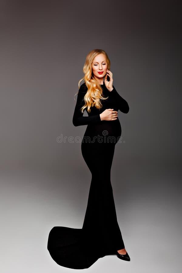 Gl?ckliche schicke junge schwangere Frau im stilvollen schwarzen Kleiderholding-Bauchsto? und Aufstellung im Licht Stilvolle mode lizenzfreies stockbild