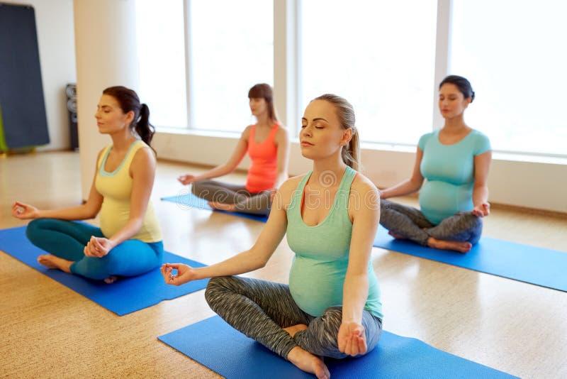 Gl?ckliche schwangere Frauen, die am Turnhallenyoga meditieren lizenzfreies stockbild