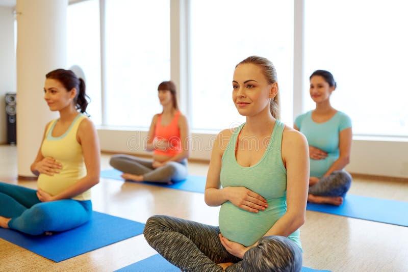 Gl?ckliche schwangere Frauen, die am Turnhallenyoga trainieren stockfoto