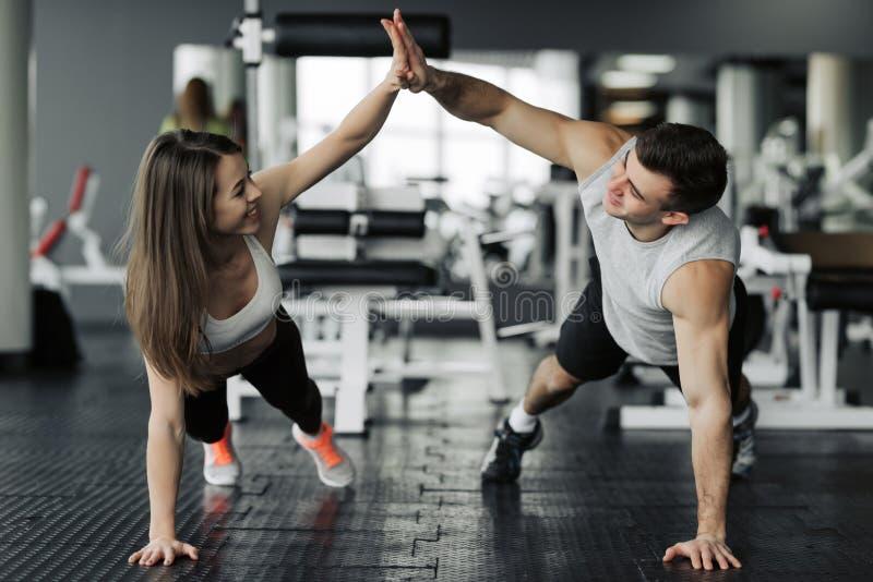 Gl?ckliche sportliche Paare, die miteinander Hoch f?nf geben, beim Handeln sich oben zusammen Turnhalle eindr?cken Sie Einheit un stockfotos