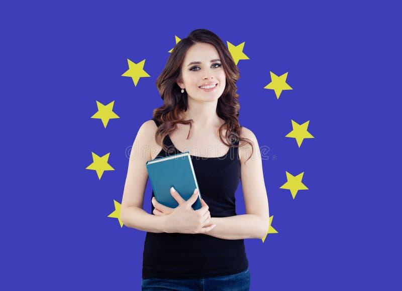 Gl?ckliche Studentin mit Buch gegen den Flaggenhintergrund der Europ?ischen Gemeinschaft lizenzfreie stockbilder