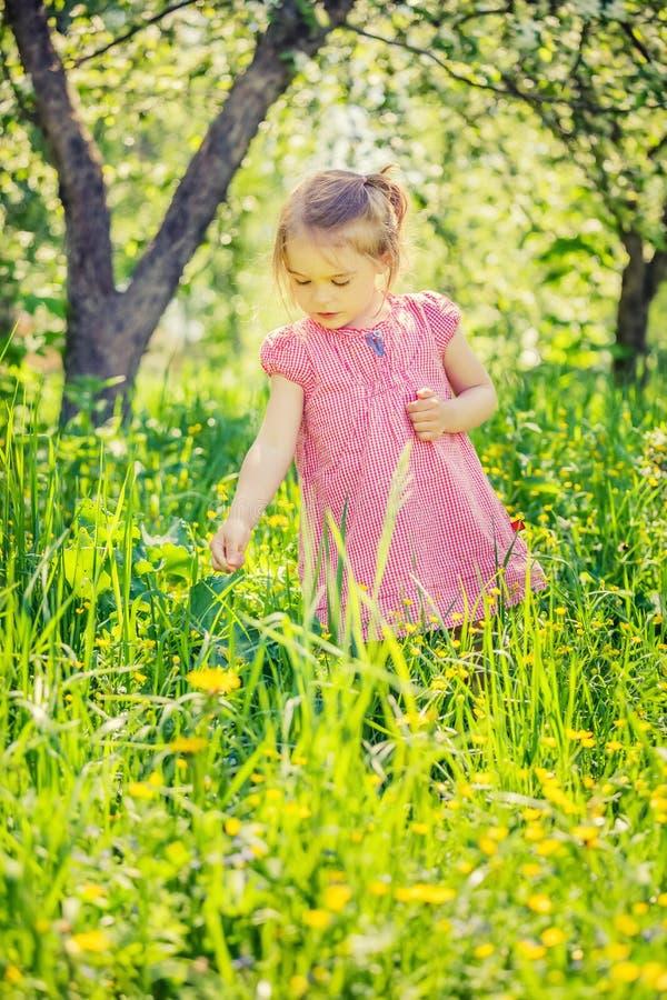 Gl?cklicher Garten des kleinen M?dchens im Fr?hjahr stockfoto
