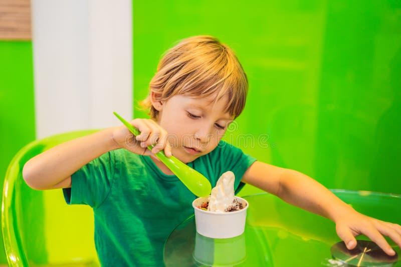 Gl?cklicher Junge, der eine geschmackvolle Eiscreme oder einen gefrorenen Jogurt isst lizenzfreies stockbild