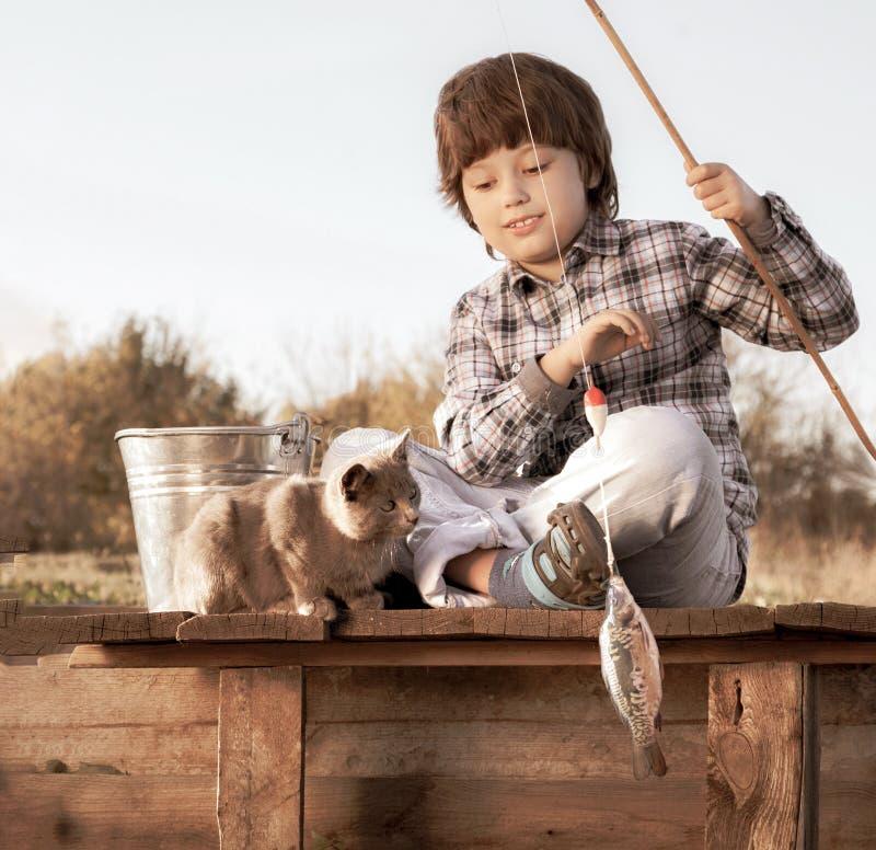 Gl?cklicher Junge gehen, auf dem Fluss mit Haustier, Kindern eins und K?tzchen des Fischers mit einer Angelrute auf dem Ufer des  stockbilder