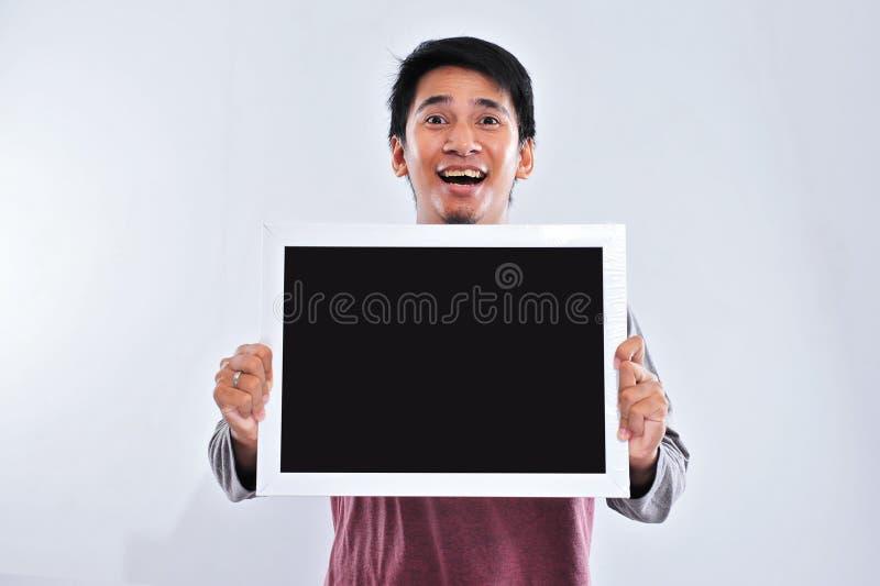 Gl?cklicher junger h?bscher asiatischer Mann, der die leere Tafel oder Brett bereit zu Ihrem Text h?lt und zeigt lizenzfreies stockfoto