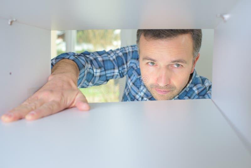 Gl?cklicher junger Mann, der inneren Kasten schaut stockfotos