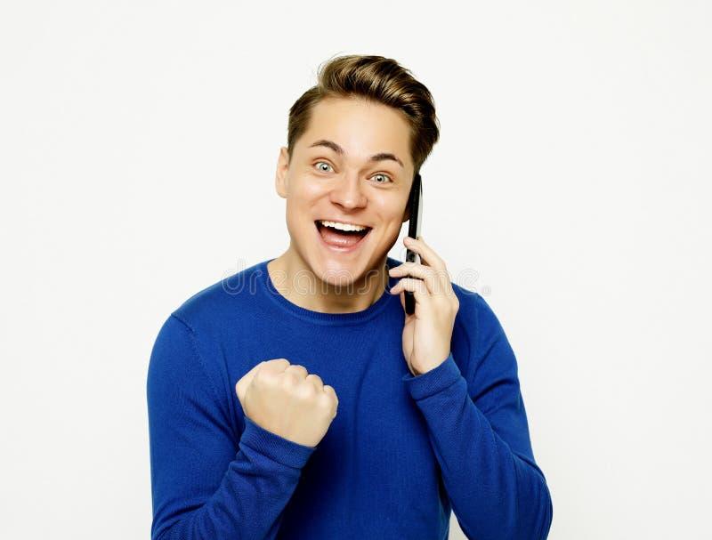 Gl?cklicher junger Mann im Hemd gestikulierend und bei der Unterhaltung l?chelnd am Handy stockfotografie