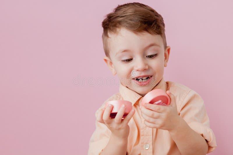 Gl?cklicher kleiner Junge mit einem Geschenk Foto lokalisiert auf rosa Hintergrund L?chelnder Junge h?lt Pr?sentkarton Konzept vo stockfotos