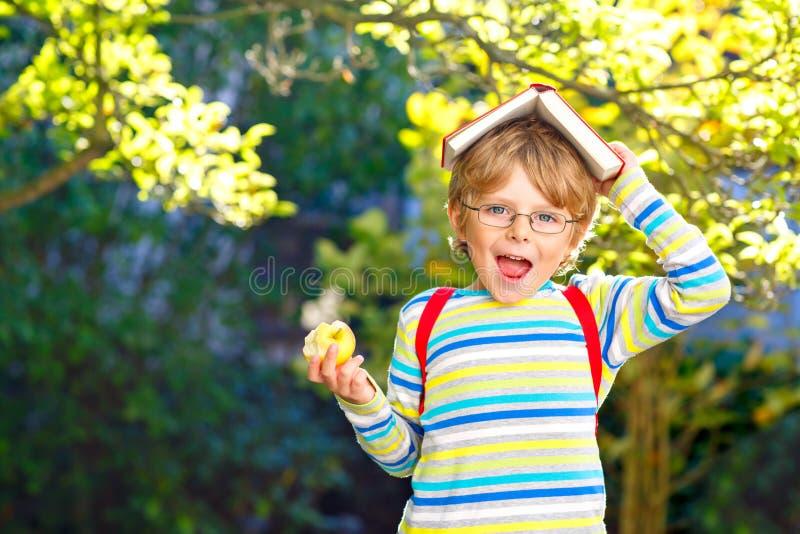Gl?cklicher kleiner Vorschulkinderjunge mit Gl?sern, B?chern, Apfel und Rucksack an seinem ersten Tag zur Schule oder zur Kindert stockfotografie