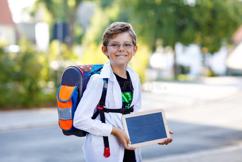 Gl?cklicher Kleinkindjunge mit Gl?sern und Rucksack oder Schultasche Schulkind auf dem Weg zur Schule Gesundes entz?ckendes Kind stockbilder