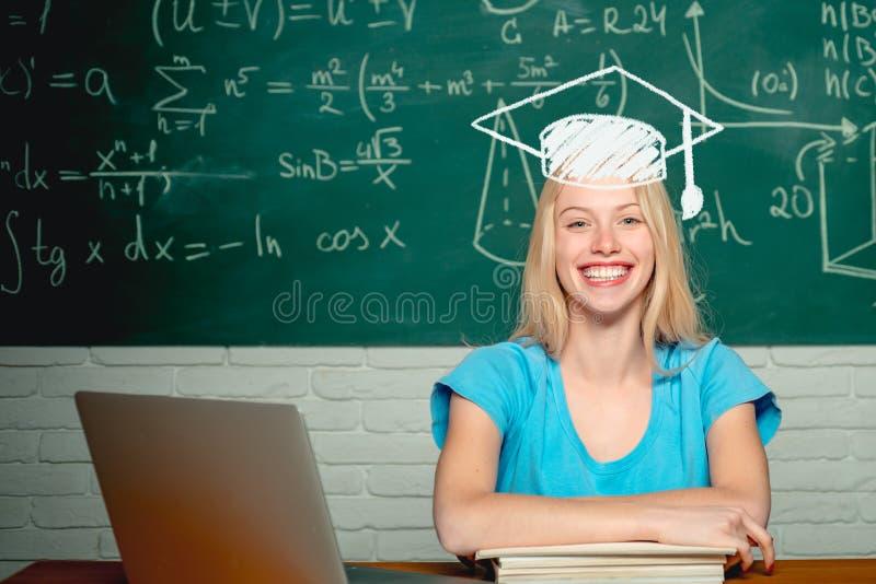 Gl?cklicher Kursteilnehmer Frau, die an Laptop-Computer ?ber Tafelhintergrund arbeitet Student Student, der bei Tisch sitzt stockfoto