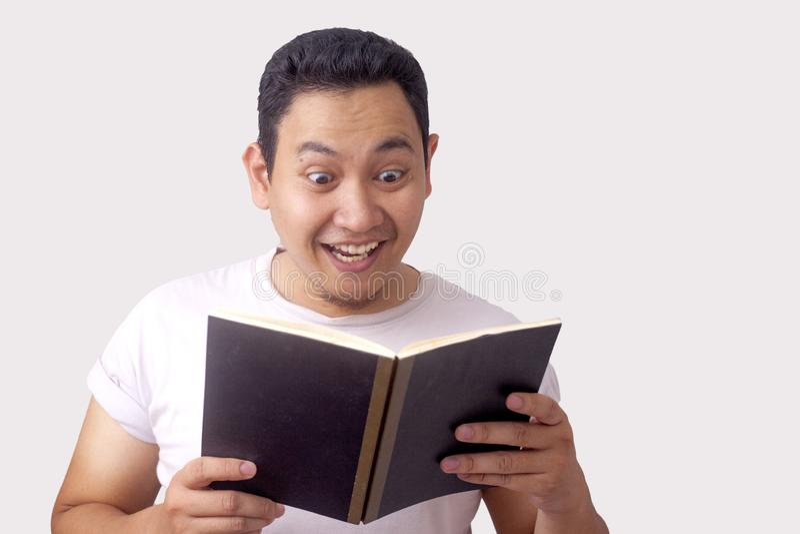 Gl?cklicher l?chelnder Mann w?hrend Ablesen-Buch stockbild