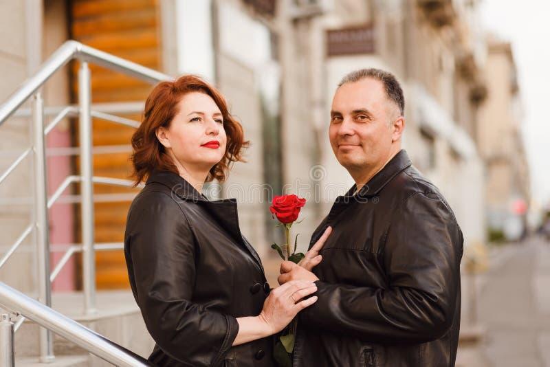 Gl?cklicher Mann und Frau von mittlerem Alter, die rote Rose h?lt Liebe in der Stadt stockfotografie