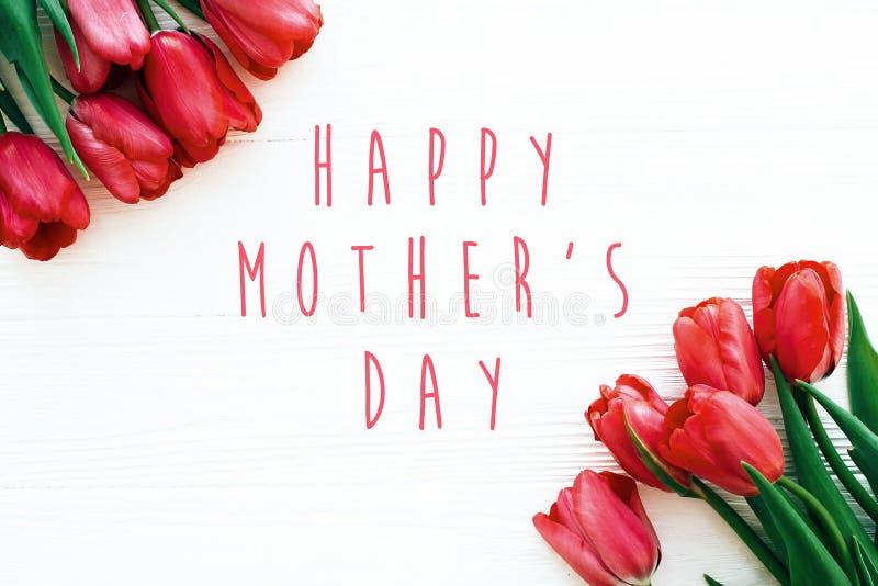 Gl?cklicher Muttertagtext und sch?ne rote Tulpen auf dem wei?en h?lzernen flachen Hintergrund legen Gl?ckliche Muttertagesgru?kar stockbilder