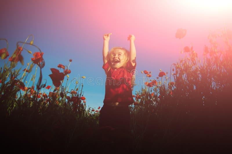 Gl?cklicher Sommer Lustige Stämme auf dem Mohnblumengebiet Gl?ckliches Kind auf Naturhintergrund Sonniger Tag Vollkommenes Wetter stockfotos