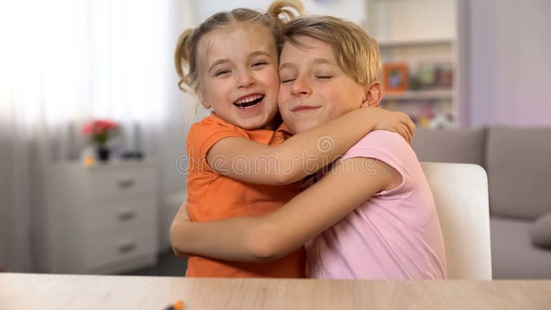 Gl?cklicher umarmendes Junge und M?dchen, Bruderschwestern?he, zarte Familienbeziehungen lizenzfreie stockfotografie