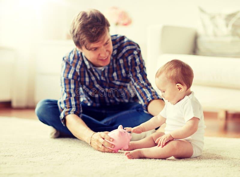 Gl?cklicher Vater mit Baby und Sparschwein zu Hause lizenzfreies stockbild