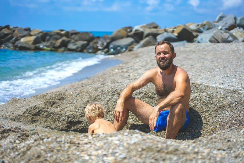 Gl?cklicher Vater und Sohn, die den Spa? spielt auf dem Strand hat stockfotos