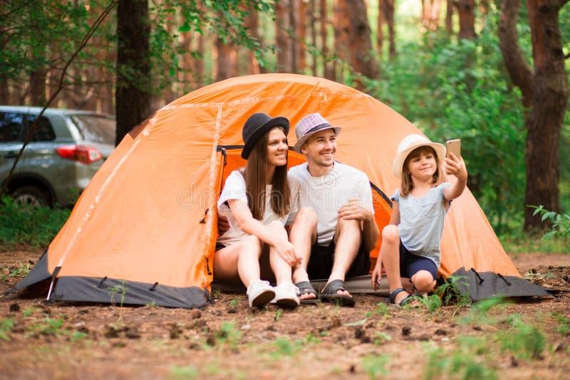 Gl?ckliches Familien-Portrait Kampieren, Wanderung, Technologie und Leutekonzept - glückliche Familie mit dem Smartphone, der sel lizenzfreie stockfotos