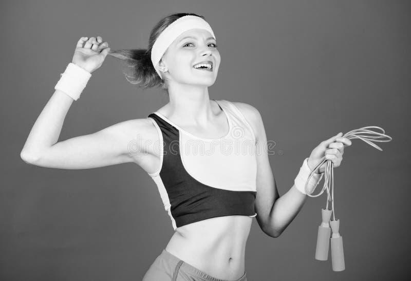 Gl?ckliches Frauentraining mit Seilspringen Sportliches Frauentraining in der Turnhalle Gesundheitsdi?t Formung des Erfolgs Stark stockbilder