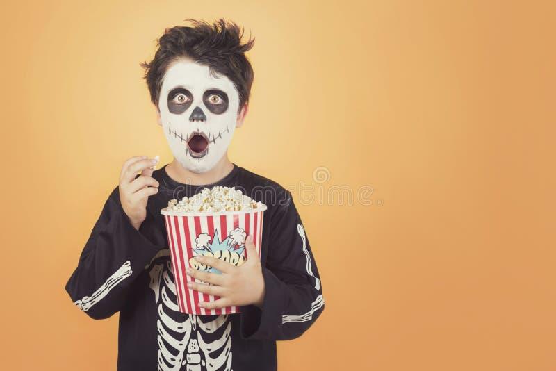 Gl?ckliches Halloween Überraschtes Kind in einem Skelettkostüm mit Popcorn lizenzfreies stockfoto