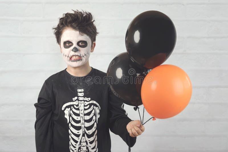 Gl?ckliches Halloween lustiges Kind in einem Skelettkostüm mit bunten Ballonen stockfotografie