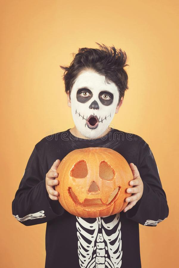 Gl?ckliches Halloween lustiges Kind in einem Skelettkostüm mit Halloween-Kürbis vorbei auf seinem Kopf stockbilder