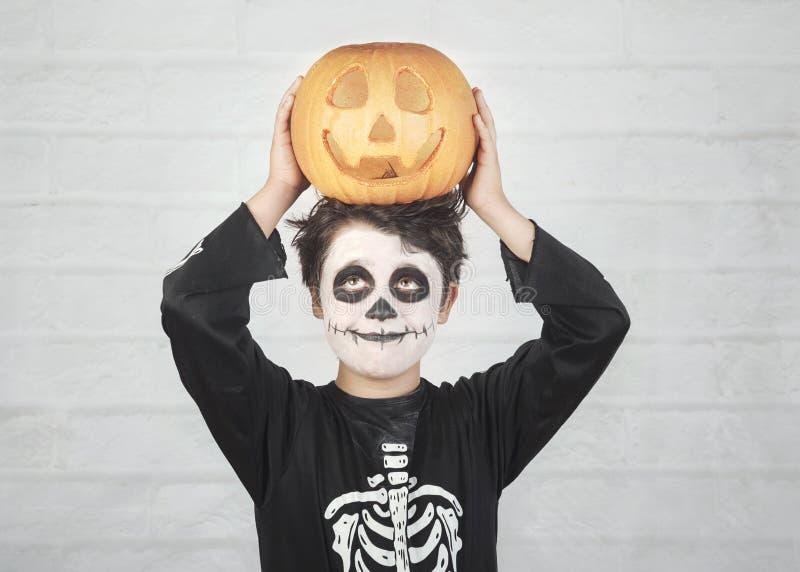 Gl?ckliches Halloween lustiges Kind in einem Skelettkostüm mit Halloween-Kürbis vorbei auf seinem Kopf lizenzfreies stockfoto