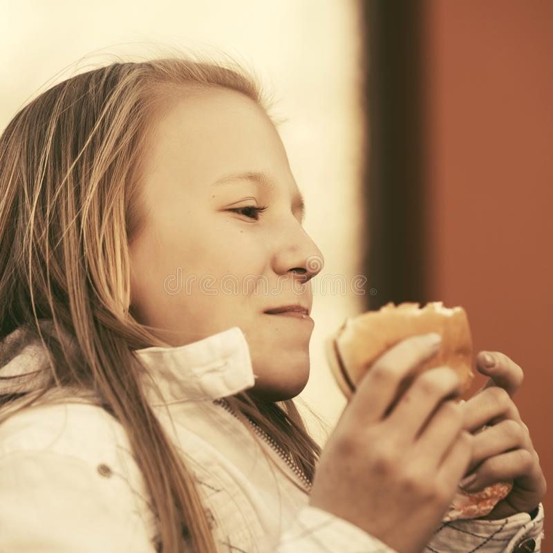 Gl?ckliches jugendlich M?dchen, das einen Burger isst lizenzfreies stockfoto