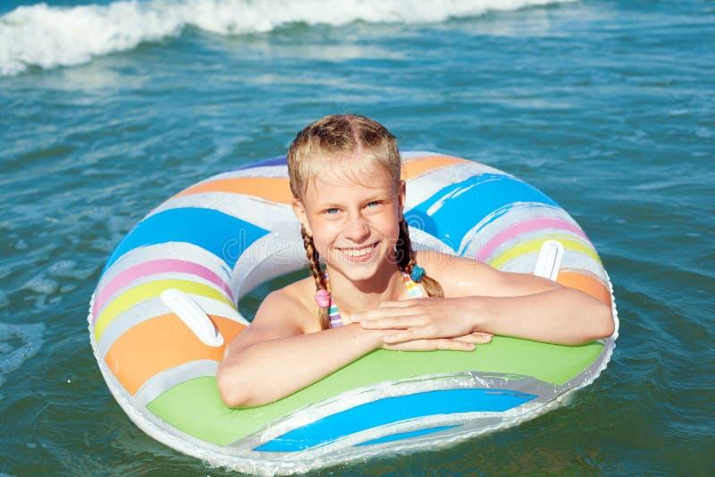 Gl?ckliches Kind, das im blauen Wasser von Ozean auf einem tropischen Erholungsort in dem Meer spielt Nettes Schwimmen des kleine lizenzfreies stockfoto