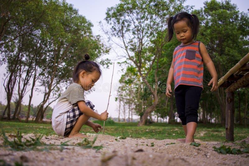 Gl?ckliches Kind, das mit Sand, lustige asiatische Familie in einem Park spielt lizenzfreies stockfoto