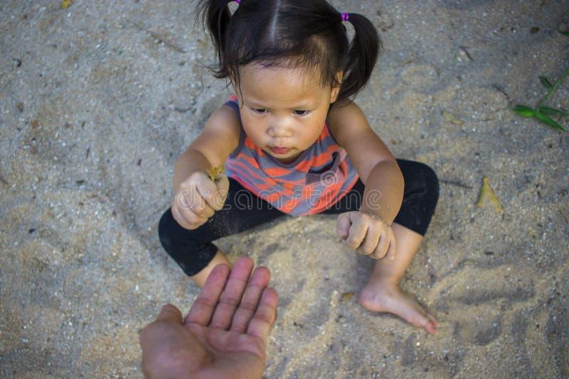 Gl?ckliches Kind, das mit Sand, lustige asiatische Familie in einem Park spielt stockbild