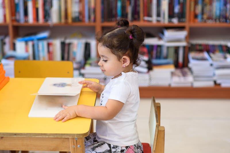 Gl?ckliches Kinderkleines M?dchen, das ein Buch liest stockbilder