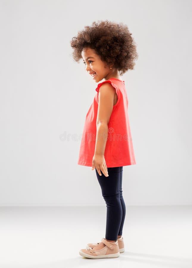 Gl?ckliches kleines Afroamerikanerm?dchen ?ber Grau stockfoto