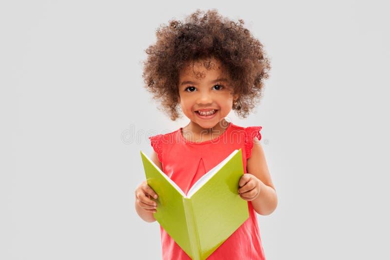 Gl?ckliches kleines Afroamerikanerm?dchen-Lesebuch lizenzfreie stockfotos