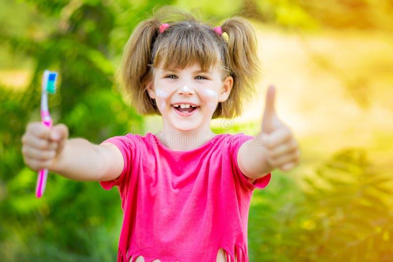 Gl?ckliches kleines M?dchen, das ihre Z?hne mit den Daumen oben putzt Zahnmedizinische Hygiene lizenzfreie stockfotografie