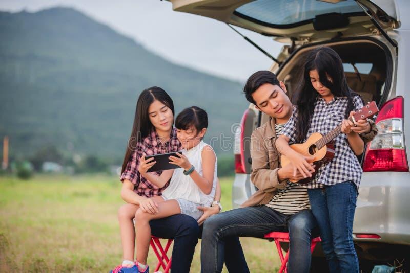 Gl?ckliches kleines M?dchen, das Ukulele mit der asiatischen Familie sitzt im Auto f?r das Genie?en von Autoreise- und Sommerferi stockfotos